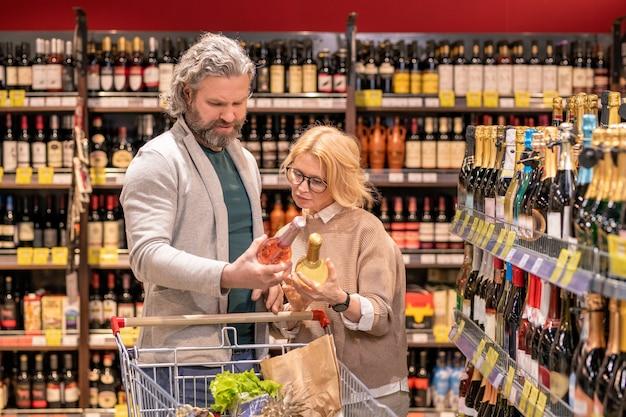 슈퍼마켓에서 두 병을 알코올 음료와 비교하면서 와인을 선택하는 쇼핑 카트와 성숙한 남편과 아내