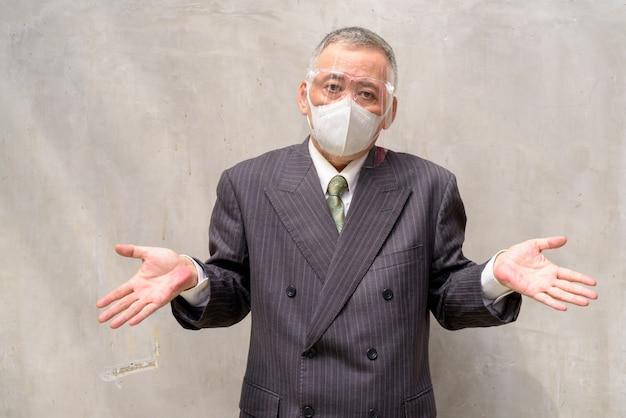 肩をすくめてマスクと顔のシールドを持つ成熟した日本のビジネスマン