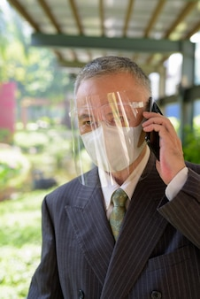 Зрелый японский бизнесмен с маской и защитной маской разговаривает по телефону в парке