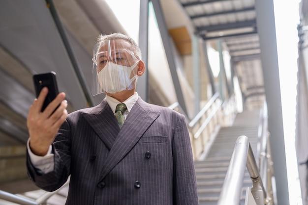 Зрелый японский бизнесмен с маской и защитной маской с помощью телефона при спуске по лестнице