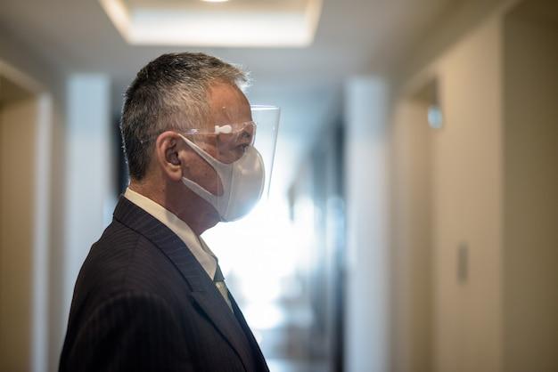 エレベーターを待っているマスクと顔のシールドを持つ成熟した日本のビジネスマン