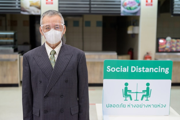 Mature japanese businessman with mask and face shield social distancing at food court