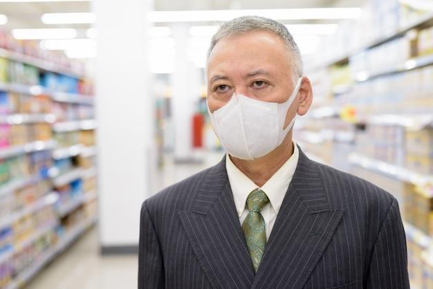 スーパーで距離を置いて買い物マスクを持つ成熟した日本のビジネスマン