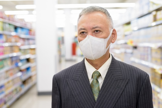 Mature japanese businessman with mask shopping with distance at the supermarket