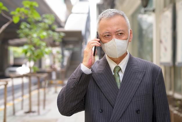 Зрелый японский бизнесмен с маской разговаривает по телефону в городе