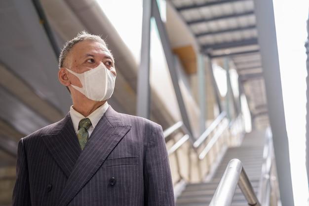 Зрелый японский бизнесмен с маской мышления при спуске по лестнице в городе