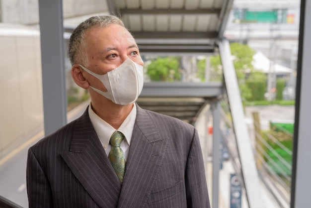Mature japanese businessman with mask thinking while going up the stairs in the city