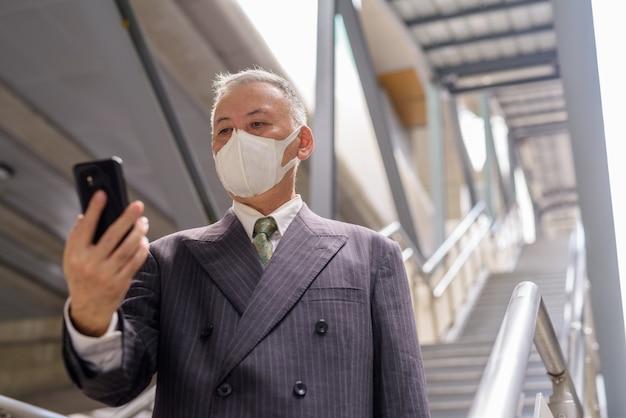 Зрелый японский бизнесмен с маской с помощью телефона при спуске по лестнице в городе