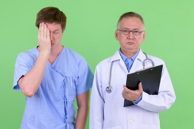 緑の壁とクロマキーに対して一緒に成熟した日本人男性医師とスカンジナビアの男性患者