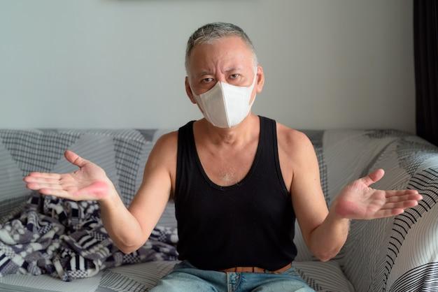 検疫下で自宅で肩をすくめマスクを持つ成熟した日本人男性
