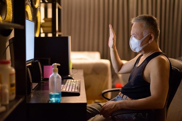 家で残業しながらマスクビデオ通話を持つ成熟した日本人男性