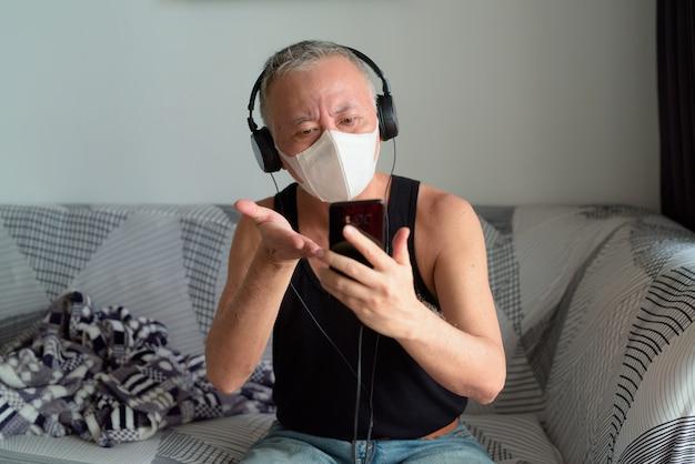検疫下で自宅でヘッドフォンでマスクビデオ通話を持つ成熟した日本人男性