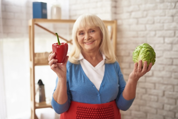 Mature lady holds cabbage and pepper vegan food.
