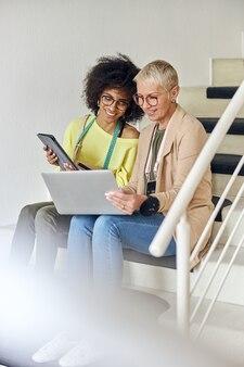 成熟した女性は、タブレットを保持している笑顔のアフリカ系アメリカ人のファッションデザイナーにラップトップで情報を表示します