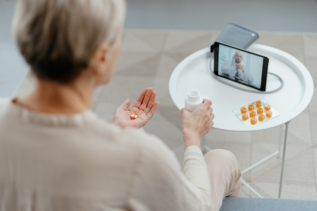 Mature lady taking pills under the supervision of a doctor