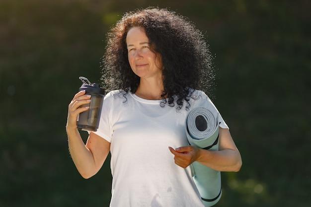 成熟した女性が夏の公園でトレーニングします。ヨガをやっているブルネット。スポーツ服の老婆。