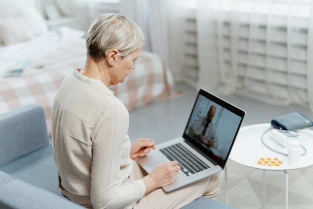Mature lady using laptop for video consultation with her doctor