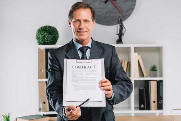 Зрелый адвокат, указывающий на место подписи на контрактном документе с ручкой