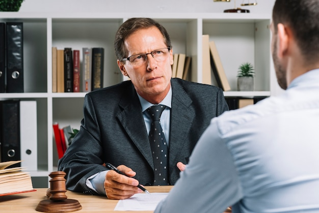 Mature lawyer with clients in a meeting