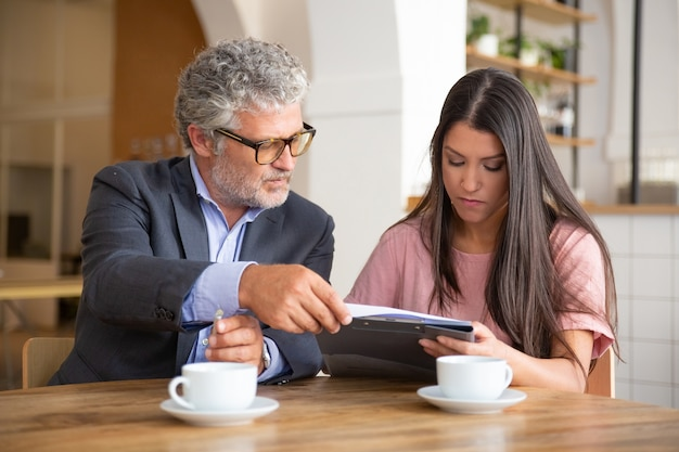 Mature legal advisor helping young customer to complete document form