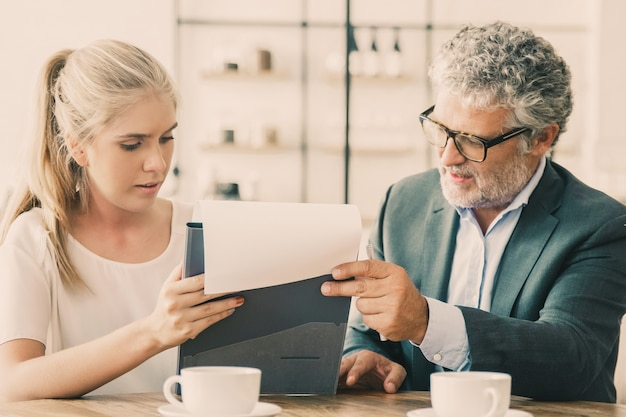 Mature legal advisor reading document and explaining details to young customer.