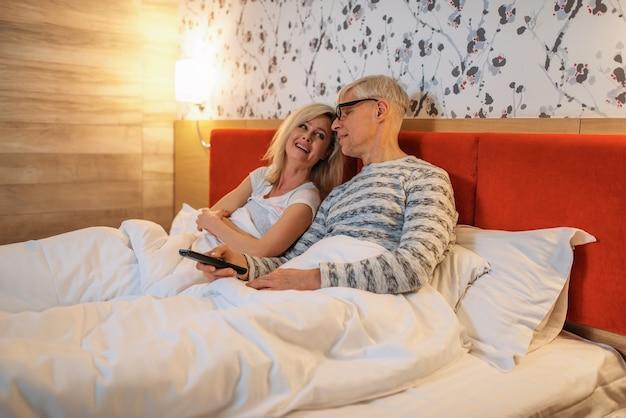 成熟した愛のカップルが寝室でテレビを見て