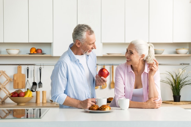 Mature loving couple family standing at the kitchen