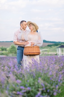 라벤더 밭에서 사랑하는 성숙한 부부, 서서 껴안고 서로를 바라보고