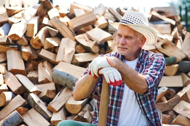 Зрелый лесоруб отдыхает после раскалывания древесины