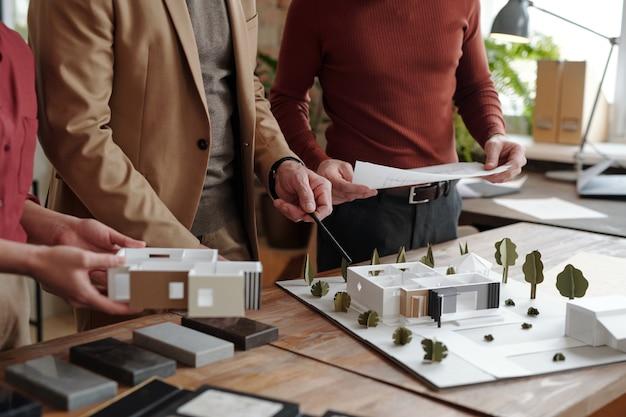 Зрелый мужчина-архитектор с карандашом, указывая на модель нового дома, в то время как его молодые коллеги держат бумагу с эскизом и частью плана