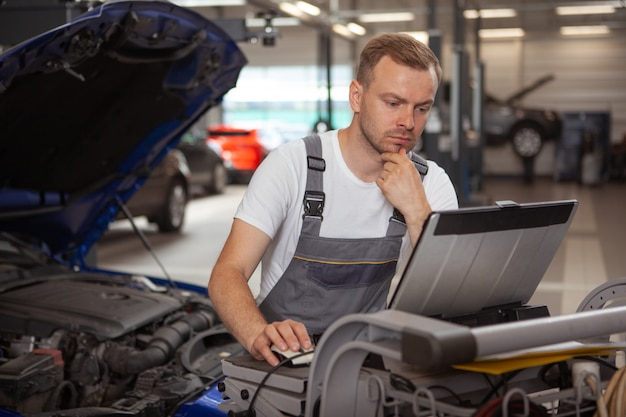 Mature male auto mechanic working at the garage