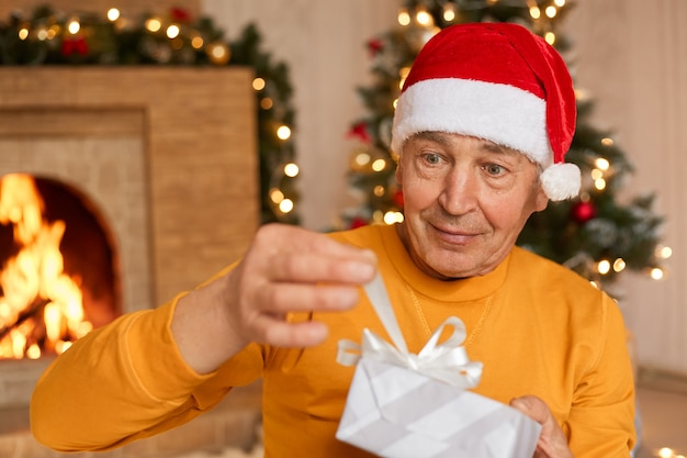 Mature male celebrating christmas at home, opening present box with ribbon, being surprised, being photographed in living room with fireplace.