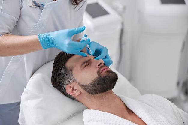 Пожилой клиент-мужчина проходит болезненную процедуру подтяжки бровей