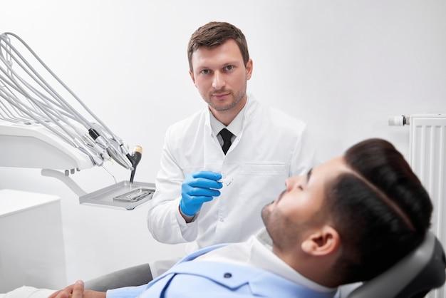 彼の男性患者の歯を調べる準備をしている仕事中の成熟した男性歯科医
