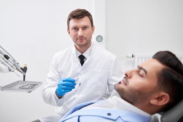 成熟した男性歯科医が自信を持って彼の患者の歯科口腔検診医師専門職との作業中に経験職業医療医学概念。