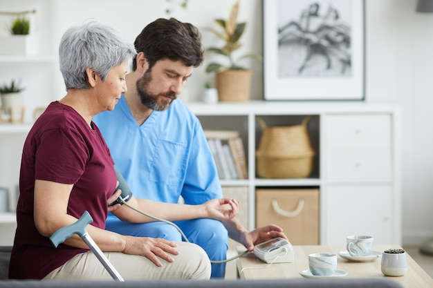 Mature male doctor examining the blood pressure of senior woman while they sitting on sofa at home