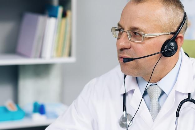 Зрелый мужчина-врач в очках носит беспроводную гарнитуру, разговаривает с пациентом больницы по видеосвязи