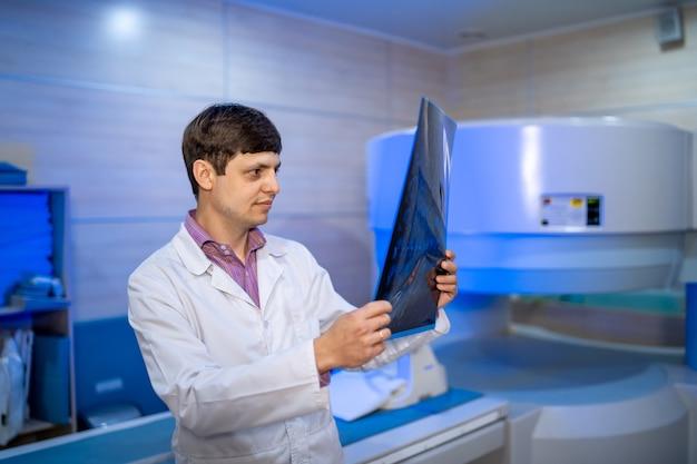 現代のオフィスの背景に分離されたx線を見て成熟した男性医師。ヘルスケア、レントゲン、人と薬の概念。