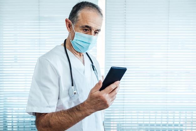 Зрелые мужчины-врач - медсестра в маске, глядя на мобильный телефон рядом с окном больницы. covid-19 и концепция медицины