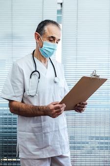 Зрелый мужчина-врач - медсестра в маске, разговаривает по мобильному телефону и держит отчет рядом с окном больницы. covid-19 и концепция медицины