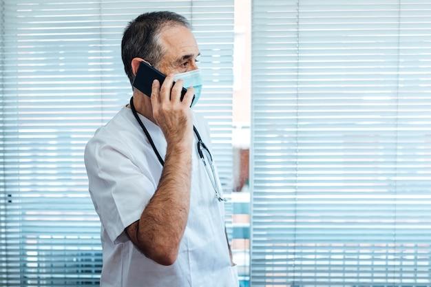 Зрелый мужчина-врач - медсестра в маске, разговаривает по мобильному телефону рядом с окном больницы. covid-19 и концепция медицины