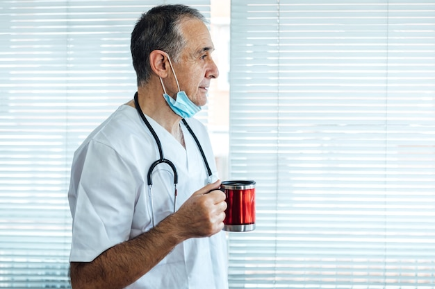 성숙한 남성 의사-간호사 병원 창에서 커피를 마시고 그의 턱에 마스크를 쓰고. covid-19 및 의학 개념