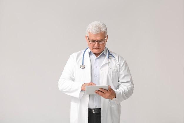 Зрелый мужчина-врач с планшетным компьютером на серой поверхности