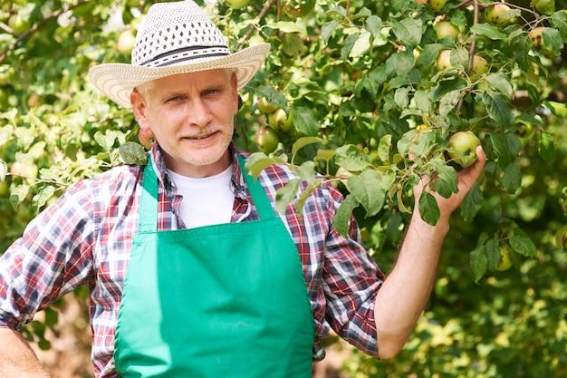 リンゴの木を持つ成熟した男性農家