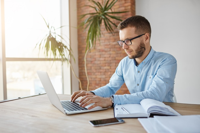 Mature male freelance web designer sitting in co-working space, working on laptop computer, writing down tasks in notebook