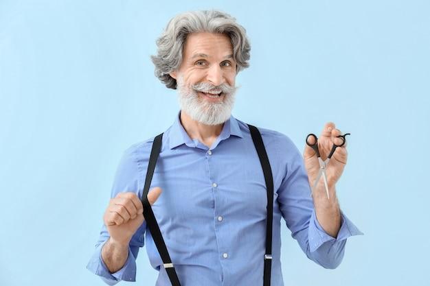 Зрелый мужской парикмахер на цветном фоне