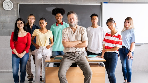 カメラを見ている10代の学生の彼の多民族のグループを持つ成熟した男性の高校教師。横長のバナー画像。教育の概念。