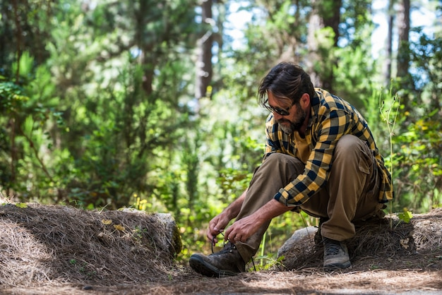 선글라스를 끼고 신발끈을 묶고 바위 위에 앉아 있는 동안 숲에서 트레킹할 준비를 하는 성숙한 남성 등산객. 자연에서 긴 하이킹 여행을 하기 전에 숲에서 하이킹 신발끈을 묶는 남자