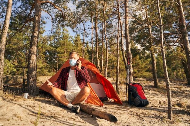 Зрелый мужчина в медицинской маске сидит возле палатки на природе и разговаривает по мобильному телефону