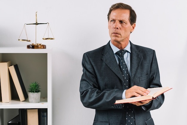 Зрелый мужчина-юрист, имеющий юридическую книгу, стоящую в зале суда